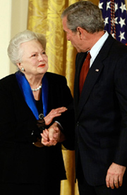 Olivia de Havilland shakes hands with President George W. Bush in a formal setting with US flag visible
